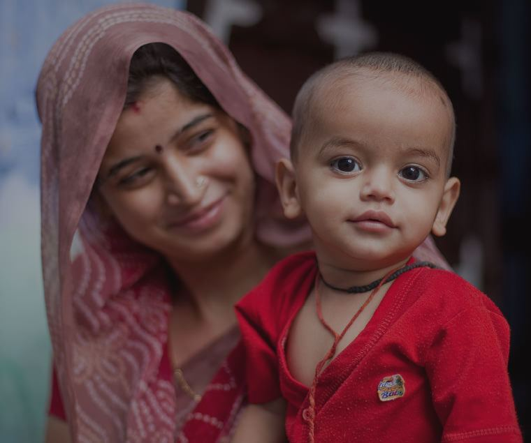 Smiling Indian woman with a veil holding a child